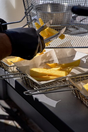 Cooking french fries. Closeup view of making french fries deep frying in fast food. The concept of fast food, delicious food, restaurant. Street market, street trading, healthy food. Selective focus.