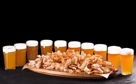 Beer set for a large group of friends. Beer in glasses closeup on the concrete table. Beer and snacks are crispy chips on a wooden tray. Copy space. Drink and snack for the football match or party.