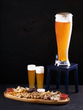 Beer set for a large group of friends. Beer in glasses closeup on the concrete table. Beer and snacks - chips, crackers and cold cuts with sauce on a wooden tray. Copy space. Drink and snack for the football match or party. Stock Photo