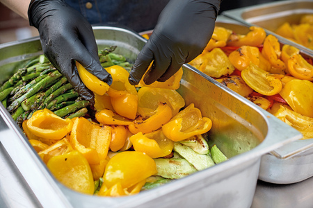 Grilled vegetables in a large container in the kitchen, the cook interferes with the hands of vegetables. Street market, street trading, healthy food. Selective focus. Close up.