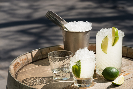 summer drink with lime and alcohol in a carafe and a fougere with ice on a wooden barrel, daylight outside, copy space.