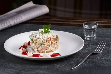 Russian traditional salad Olivier with vegetables and meat. restaurant dish, New Years salad on a white plate and a glass of vodka. Close-up. Gray background