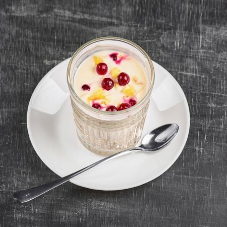 healthy nutritious breakfast with fresh cranberries and yogurt, cottage cheese. Cranberry, vitamin smoothies in a glass. Restaurant, food menu, recipe, cafe concept. Free copy space for text.