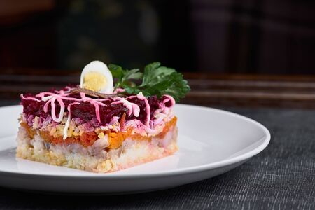 Herring salad under a fur coat with crabs on a white plate. Layered salad with herring, beets, carrots, onions, potatoes and eggs. Traditional Russian cuisine, Herring under a fur coat shuba close-up and copy space.