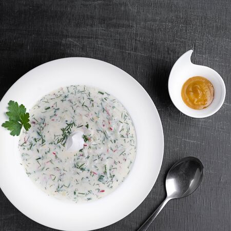 Summer Cold soup with fresh cucumbers, radishes with yoghurt in bowl on wooden background. Traditional russian food - okroshka. Vegetarian meal. Top view. Flat lay. Okroshka. 1:1 Imagens