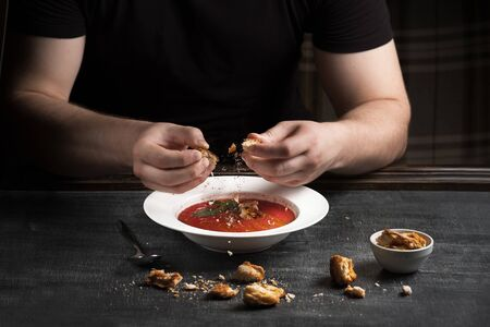 Summer fresh healthy, spicy, cold, tomato gazpacho soup with basil bread and onions, served on a dark table. . Mens hands with bread over a plate, Spanish cuisine close-up.