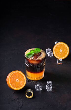 Michelada Mexican beverage made with beer. refreshing summer drink of dark beer, lime juice, oranges and ice in a glass goblet on a dark background