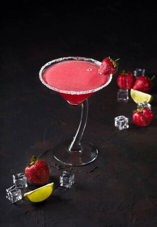 Glass of delicious Strawberry Margarita or Daiquiri with lime and ice cubes on Dark background, copy space, summer cocktail.