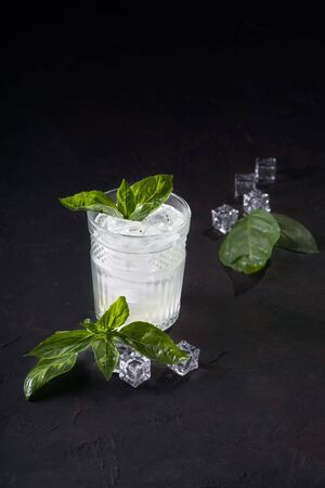 Gin or vodka with mint slices of lemon and ice on a dark background. Alcohol cocktail with citrus and basil. Copy space.