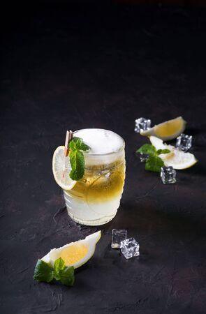 Cocktail Mule de Moscou sur fond sombre. Boisson froide, couches blanches et jaunes avec de la vodka, de la bière de gingembre épicée et du jus de citron vert. Mise au point sélective. Carte de cocktail. Espace de copie. Banque d'images
