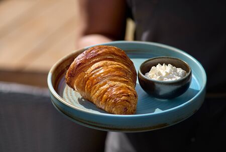 Breakfast concept. Morning, Healthy breakfast. Freshly baked croissants with cream cheese in a blue plate on the table copy space, selective focus. 版權商用圖片