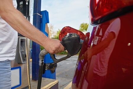 Man refuses his red car with gasoline at a gas station. Hand and black refueling gun close up Stockfoto