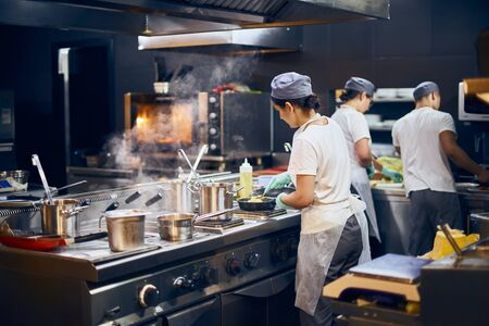 the team of cooks backs in the work in the modern kitchen, the workflow of the restaurant in the kitchen. Copy space for text