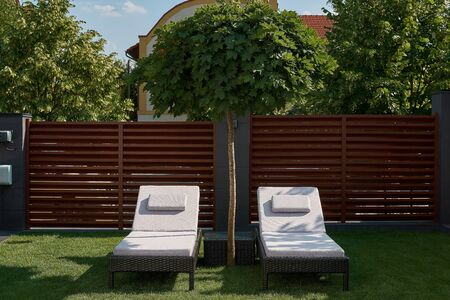 Two chaise lounges are on the green lawn in the courtyard of the house. Concept of relaxation, rest, weekend