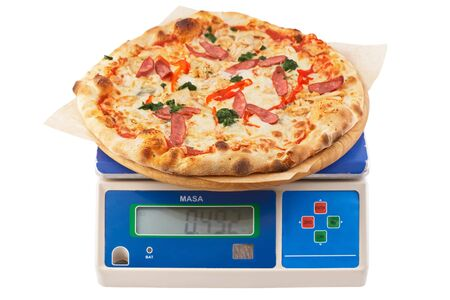 Pizza on control weight. Mario pizza with chicken, sausage and cheese. Electronic weights with pizza on an isolated white background.