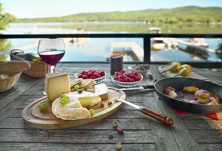 Assortment of cheese on a wooden tray with wine, on the table, house terrace the lake, by day, there are no people.