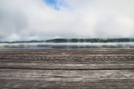 Wooden pier overlooking the morning landscape with autumn fog over Lake Massawippi, Sunrise with fog over the lake and forest, lose up.