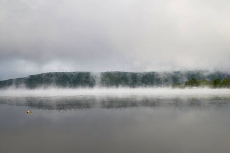 Morning landscape with autumn mist over the lake. Massawippi. Sunrise with mist over the lake and forest. Travel on Canada. Stock Photo