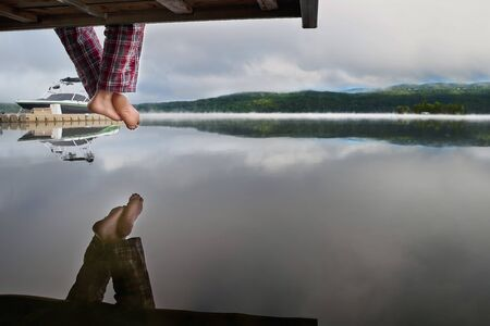 Bare feet hanging from a wooden pier above the water, with space for text design. Enjoying the sunrise over the misty lake. Travel on Canada. Stock Photo