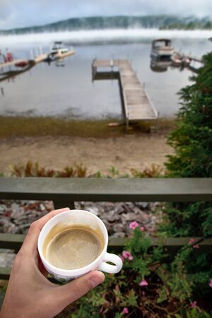 Close up of Hand man with a cup of coffee enjoying coffee looking to the horizon in a wooden balcony. a brisk morning by the misty lake. Travel on Canada.