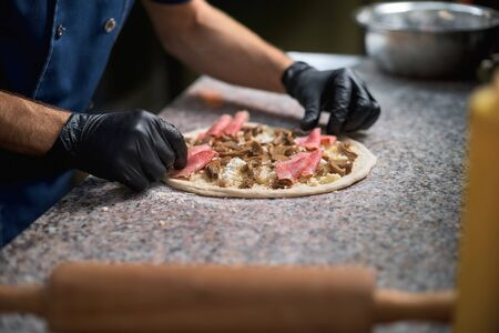 Chef prepares focaccia bread pizza baked in the oven at the market street trading on a street, healthy food Stock Photo