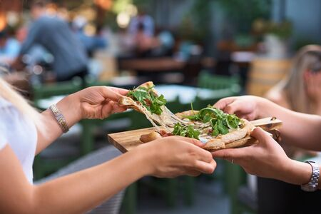 Cheese that stretches. Cheese in dough. Focaccia with cheese. Calzone with cheese. The hand that takes the piece, while standing on the terrace