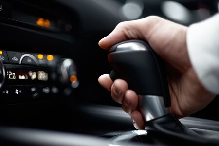 man switching gear, holding handle of the modern car, close-up view. selective focus Imagens