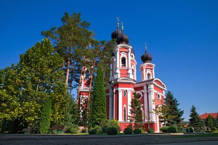 Orthodox Curchi monastery in Moldova with the sun shining at the crosses, green trees and on a sunny spring day