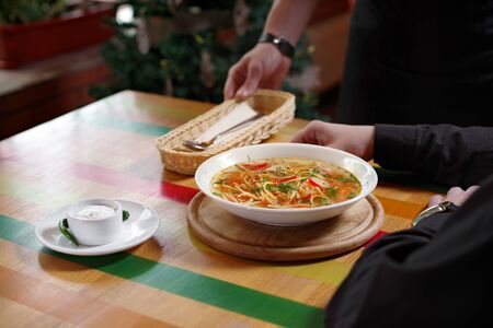 Man was served a bowl of soup with chicken, vegetables and noodles, a with sour cream and a spoon, place for text. Traditional Russian or Moldavian, Romanian or Ukrainian food is called Zama.