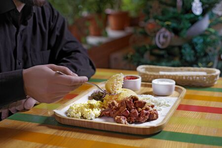 Man eats in a restaurant, close up.Traditional russian or moldavian or romanian or ukrainian food called mamaliga. Italian traditional Polenta, porridge made from cornmeal. Mamaliga With Cottage Chees 写真素材