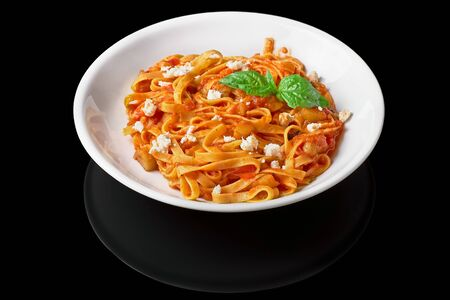 Heaped plate of delicious Italian spaghetti pasta with fresh basil leaves and cheese, on a black background Isolated. Foto de archivo