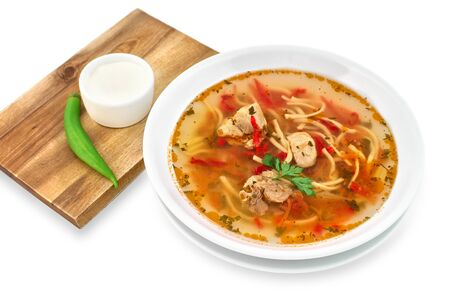 Soup with noodles, meat and vegetables, served with sour cream, Comfort Food, Zeama, traditional Moldavian and Romanian soup. on a white background, copy space.