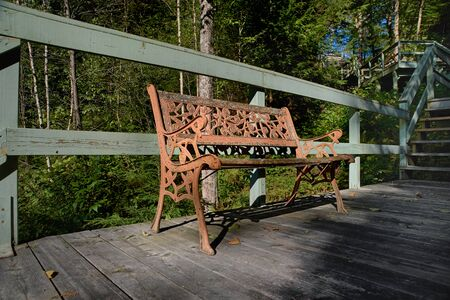 Forged metal bench on a hiking wooden path to the mountains. Sunbeams, warm autumn day with trees in the background. In Harrington, QC, Canada