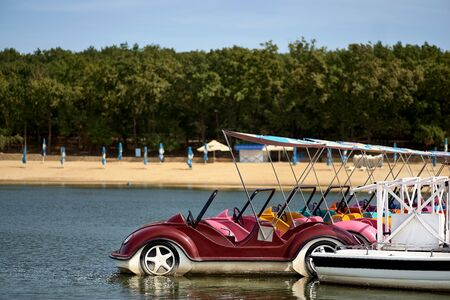 Catamarans in the form of cars at the pier on the lake