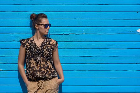 Cute girl in front of a blue wooden wall, a woman with sunglasses on a blue background. Фото со стока