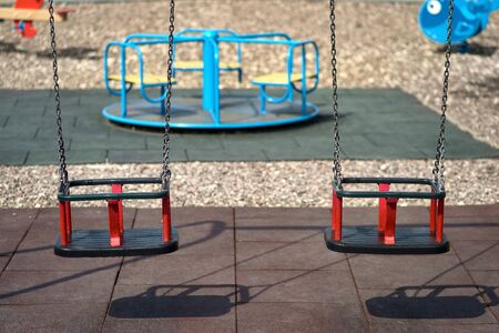 Two rubber swings weigh on a chain. Playground on a sunny day, shadow from the swing. Seats on the swing are free, there are no children on the Playground .