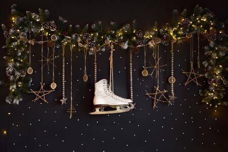 Christmas decorations on a dark wall, Happy Holiday. The wall is decorated with a garland with ate tree branches and white skates. Expectations of winter.