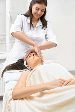 spa, resort, beauty and health concept - beautiful woman in spa salon getting face treatment, close up