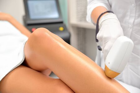 The girl is lying on the couch in the medical glasses in the treatment room. The hands of the cosmetologist make the epilation of the legs, sharpness to frame on foot