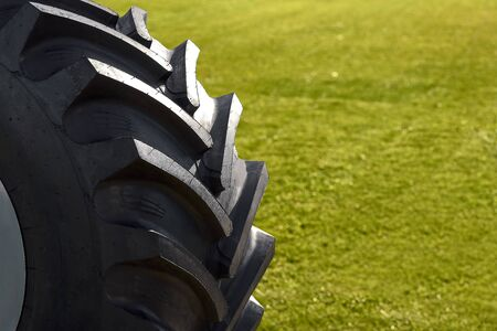 Close up of tractor tire, selective focus. wheel on a background of green grass Stockfoto
