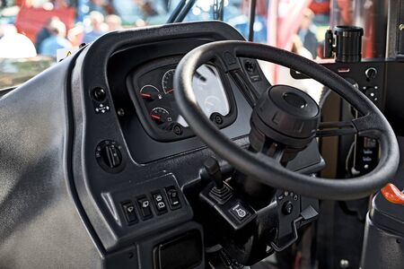 Steering wheel and the controls in the cabin of the new tractor, view inside Industrial Vehicle.