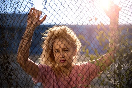 Stylish blonde posing, hands holding behind metal grid. Beautiful, hot, model, look in camera. Sun flare behind