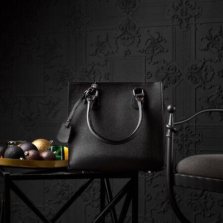 Moderne schwarze Ledertasche für eine Geschäftsfrau auf einem Couchtisch. 1:1 Kopienraum für Text und Design. Zubehör, Studioaufnahme.