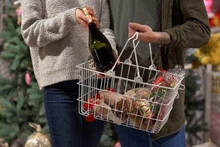 hands of a couple when buying champagne, with a shopping basket in a supermarket