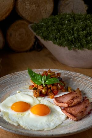 plate of fried eggs with bacon and vegetables on wooden table. English breakfast on table.
