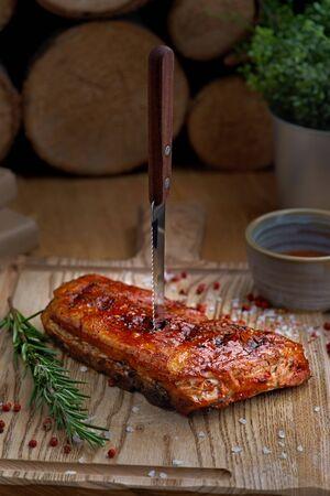 烧烤牛肉肋骨牛排配有辣椒和新鲜的蕃茄在老葡萄酒木切板上