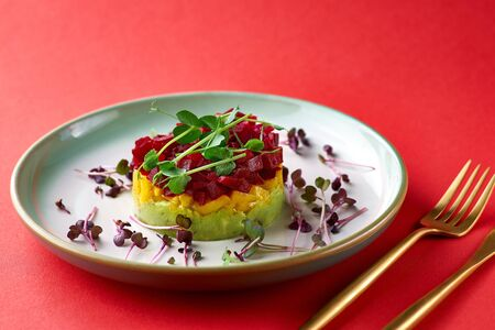 Fresh Tartar tricolor from avocado, mango and beet, selective focus. Red background
