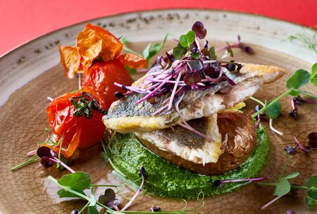 Roasted seabass fillet, served with spinach puree, peas with white onions and baked potatoes. Red background Stock Photo