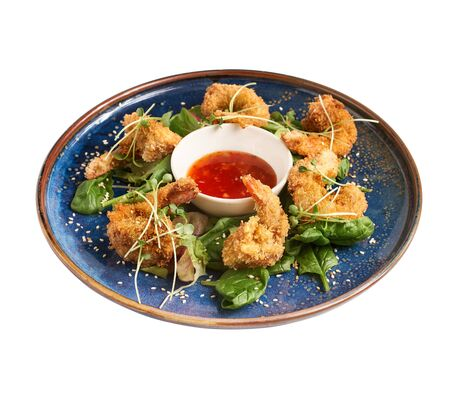 popcorn shrimp with ketchup sauce on a blue plate, isolated on white background side view.