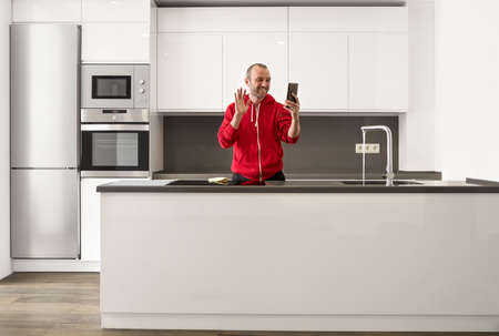 Happy man having fun and talking online video call in the kitchen at home.